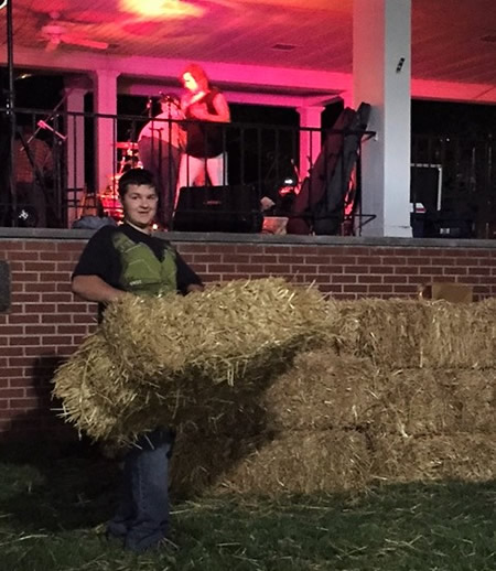 Steven picks up strawbales after the first concert of the new Downtown Concert Series