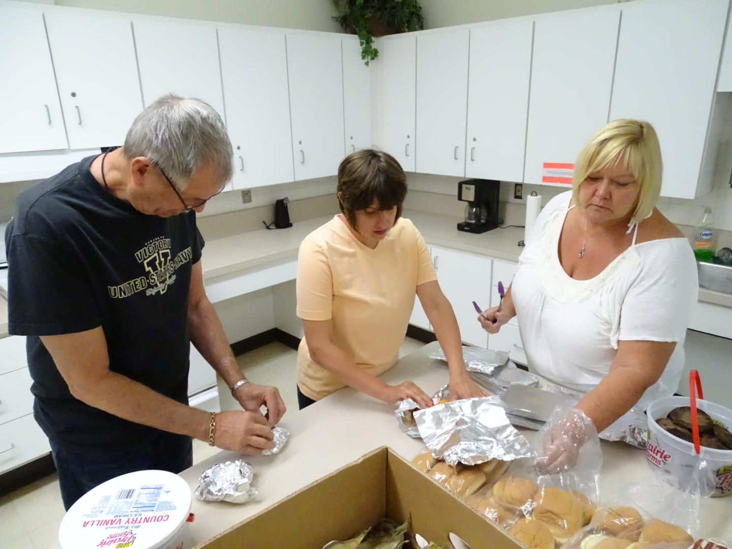 Clients help make lunches for the summer lunch bunch