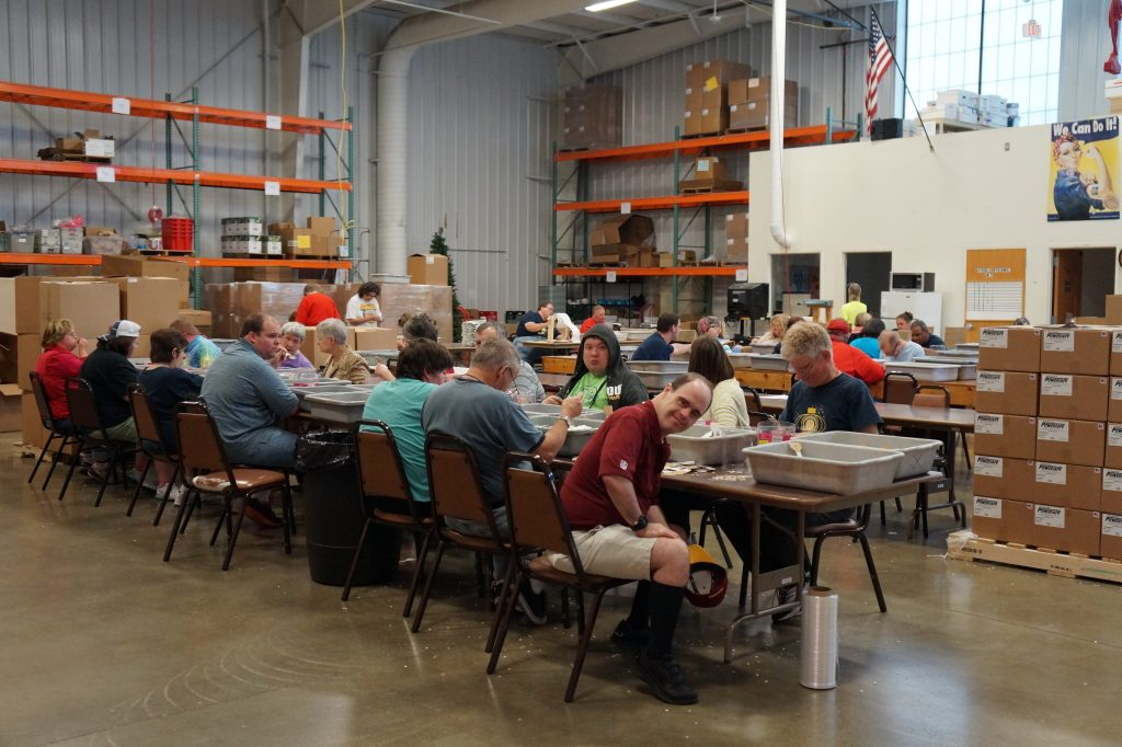 Group in warehouse workshop sitting at table.