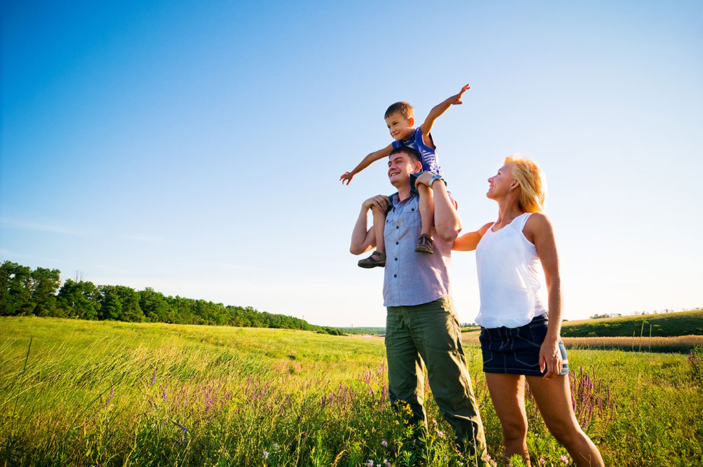 Family standing in field of tall grass.