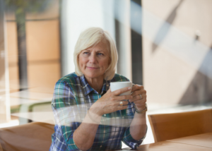 Middle aged woman at a table looking thoughtful